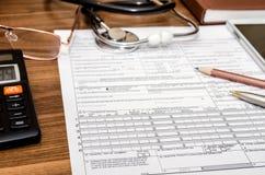 健康保险与听诊器的索赔表在剪贴板,注射器,计算器 图库摄影