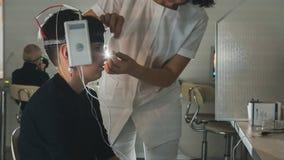 健康儿童` s诊断-男孩患者的验光师女性被投入的脑子眼睛设备-眼科学诊所 免版税库存图片