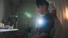 健康儿童` s诊断-验光师投入男孩患者的脑子眼睛设备-眼科学诊所 库存图片
