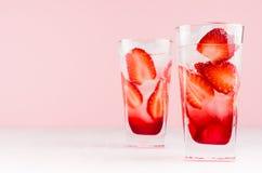 健康冷的果子饮料用草莓和矿泉水,在现代典雅的粉红彩笔内部,拷贝空间的冰 免版税图库摄影