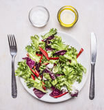 健康午餐,新鲜的沙拉在一块板材有刀子叉子、油和盐木土气背景顶视图 库存照片