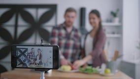 健康博克,在健康营养现场直播的vloggers年轻夫妇,当准备从菜时的有用的食物 影视素材