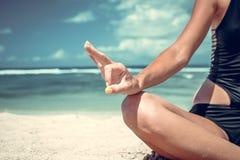 年轻健康可爱的在海滩努沙Dua的女子实践的瑜伽,热带巴厘岛,印度尼西亚 显示标志OK 免版税库存图片