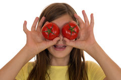 健康吃的女孩用蕃茄菜在她的眼睛 免版税图库摄影