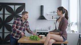 健康吃,可爱的男性准备在晚餐和女性开会的有用的素食食物在厨房用桌上与 影视素材