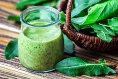 健康吃,饮料和饮食概念 美丽的开胃菜绿色圆滑的人或菠菜汁在玻璃瓶子有新鲜的叶子的求爱 免版税库存图片