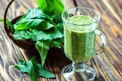 健康吃,饮料和饮食概念 美丽的开胃菜绿色圆滑的人或菠菜汁在玻璃瓶子有新鲜的叶子的求爱 免版税库存照片