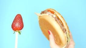 健康和不健康的食物的概念 反对汉堡包的草莓在明亮的蓝色背景 女性手与 股票视频