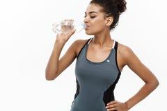 健康和健身概念-体育的美丽的非裔美国人的女孩由塑料瓶以后给饮用水穿衣 免版税库存图片
