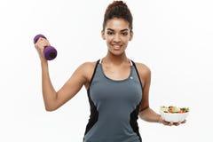 健康和健身概念-在拿着哑铃和新鲜的沙拉在手上的饮食的美丽的运动的非裔美国人 库存照片