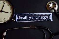 健康和愉快在与医疗保健概念启发的印刷品纸 闹钟,黑听诊器 库存照片