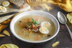 健康和温暖的冬天汤用米、红萝卜、鸡豆、鸡、火腿和煮沸的鸡蛋在土气木桌背景 免版税库存图片