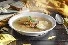 健康和温暖的冬天汤用米、红萝卜、鸡豆、鸡、火腿和煮沸的鸡蛋在土气木桌背景 库存图片