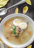 健康和温暖的冬天汤用米、红萝卜、鸡豆、鸡、火腿和煮沸的鸡蛋在土气木桌背景 免版税图库摄影