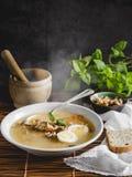健康和温暖的冬天汤用米、红萝卜、鸡豆、鸡、火腿和煮沸的鸡蛋在土气背景 免版税库存图片