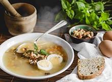 健康和温暖的冬天汤用米、红萝卜、鸡豆、鸡、火腿和煮沸的鸡蛋在土气背景 免版税库存照片