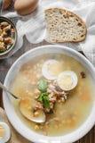 健康和温暖的冬天汤用米、红萝卜、鸡豆、鸡、火腿和煮沸的鸡蛋在土气背景 库存照片
