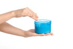 健康和身体关心题目:拿着有奶油的妇女的手一个蓝色瓶子隔绝在白色背景 免版税图库摄影