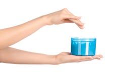 健康和身体关心题目:拿着有奶油的妇女的手一个蓝色瓶子隔绝在白色背景 免版税库存图片
