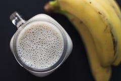 健康圆滑的人 香蕉、燕麦、Chia种子和蜂蜜混合 香蕉在背景中 顶视图 免版税库存图片