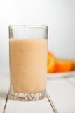 健康在木桌上的饮料橙色圆滑的人 免版税库存图片