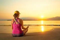 年轻健康在海滩的女子实践的瑜伽在日落 免版税库存照片