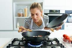健康在煎锅的年轻女人在家烹调和嗅到的食物在厨房里 免版税库存照片
