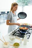 健康在煎锅的年轻女人在家烹调和混合的食物在厨房里 免版税库存图片