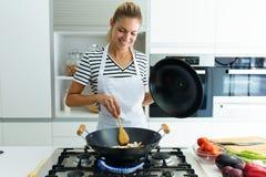 健康在煎锅的年轻女人在家烹调和混合的食物在厨房里 库存图片