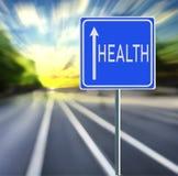健康在迅速背景的路标与日落 图库摄影