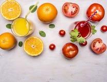 健康在玻璃的食物新鲜的汁与秸杆、桔子和蕃茄木土气背景顶视图关闭 库存照片