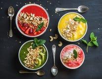 健康夏天早餐概念 五颜六色的果子圆滑的人滚保龄球与坚果、燕麦格兰诺拉麦片和薄荷叶在黑色 免版税库存图片