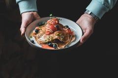 健康夏天早餐:可口美国薄煎饼用新鲜的草莓和蓝莓和蜂蜜 免版税图库摄影