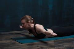 年轻健康女子实践的瑜伽户内 库存照片