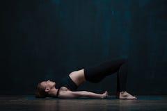年轻健康女子实践的瑜伽ondoors 免版税库存图片
