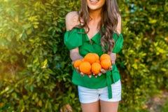 健康女孩在橙色果树园 库存图片