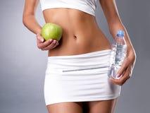 健康女性身体用苹果和水 免版税库存图片