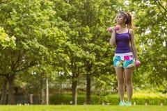 健康妇女举的哑铃在公园 免版税库存图片