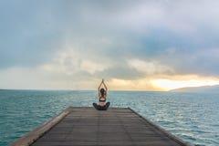 健康妇女生活方式平衡的实践在木桥梁思考和能量瑜伽在早晨海滩 免版税库存照片