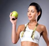 健康妇女用苹果和瓶水 免版税库存照片