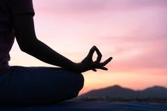 健康妇女的手和一半身体的关闭坐在莲花在日落实践的瑜伽的瑜伽位置做健康的凝思 图库摄影