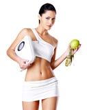 健康妇女站立与标度和绿色苹果。 免版税库存照片
