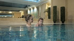 健康家庭 在水池的母亲教的女婴游泳 股票录像