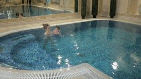 健康家庭 在水池的母亲教的女婴游泳 股票视频