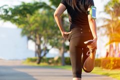健康寿命 舒展腿的亚洲健身妇女赛跑者在奔跑室外锻炼前在公园 免版税库存图片