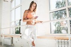 健康少妇佩带的sportwear举行智能手机在手中和在应用的计数卡路里 免版税库存照片