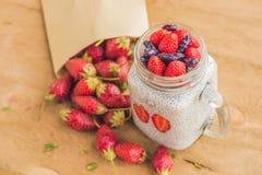 健康层状点心用chia布丁、草莓和忍冬属植物在一个金属螺盖玻璃瓶在土气背景 免版税库存图片