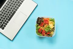 健康工作午餐在办公室,快餐的沙拉在蓝色桌上 与拷贝空间的顶视图 概念适当的营养 拿走 库存图片