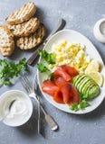 健康平衡的早餐或快餐-熏制鲑鱼、蛋沙拉和鲕梨 在灰色背景,顶视图 健康的食物 免版税库存照片