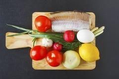 健康平衡的盘的产品集在黑背景 新鲜的有机菜和鱼在切板编结 顶视图 库存照片